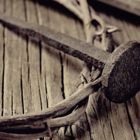 a depiction of the crown of thorns of Jesus Christ, a nail and an old scroll on the Holy Cross